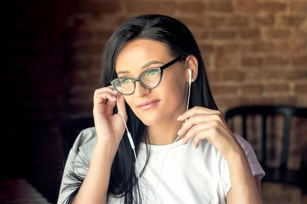 Linda mulher caucasiana de óculos, sorrindo e ouvindo música através de fones de ouvido no café.