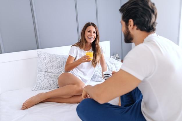 Linda mulher caucasiana de pijama, sentada na cama, bebendo suco e conversando com seu marido amoroso. homem bebendo café.