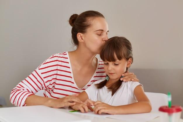 Linda mulher caucasiana e linda colegial de cabelos escuros fazendo lição de casa juntos, mamãe ajudando seu filho com a lição de casa enquanto fazia as tarefas, posando no interior de casa.
