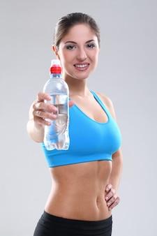 Linda mulher caucasiana em fitwear com água