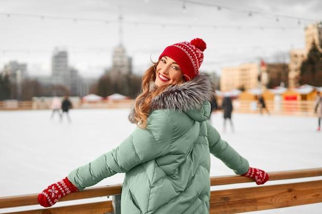 Linda mulher caucasiana em pé perto da pista de patinação no gelo