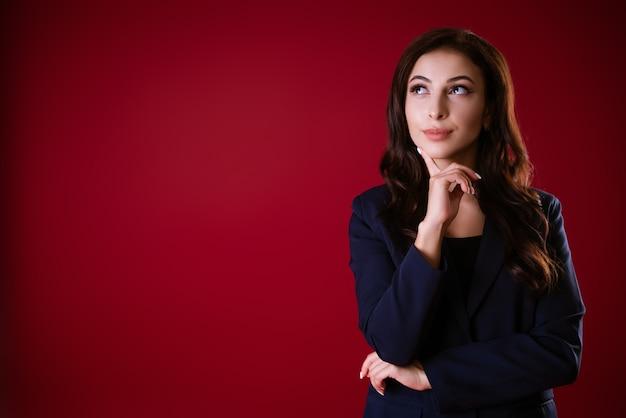 Linda mulher caucasiana em um terno sobre um fundo vermelho com um olhar pensativo toca seu queixo com ele.