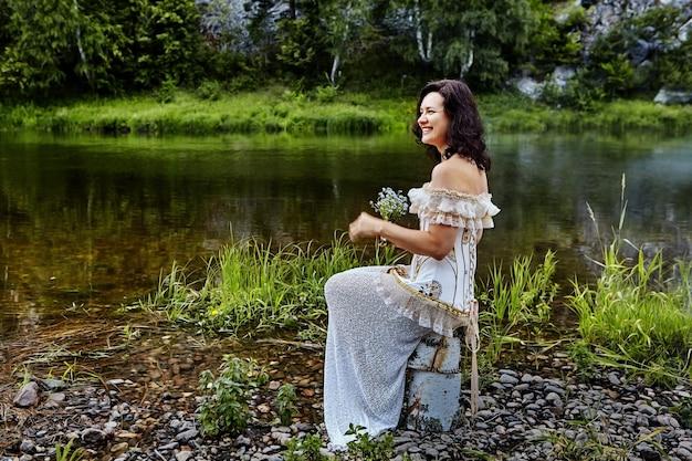 Linda mulher caucasiana em uma noite ou vestido de noiva senta-se nas margens do rio selvagem com buquê de flores silvestres nas mãos, ela ri.