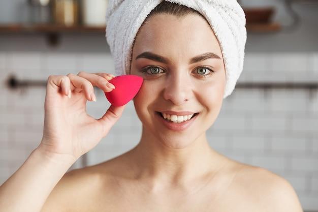 Linda mulher caucasiana enrolada em toalha branca aplicando maquiagem com esponja cosmética no apartamento