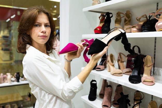Linda mulher caucasiana escolhe entre sapatos roxos e pretos e dúvidas