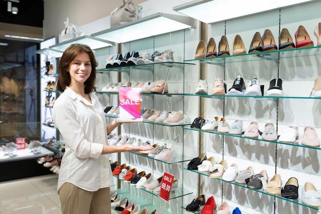 Linda mulher caucasiana mostra venda em uma loja de sapatos e sorrisos