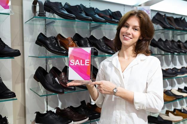 Linda mulher caucasiana mostra venda em uma loja de sapatos