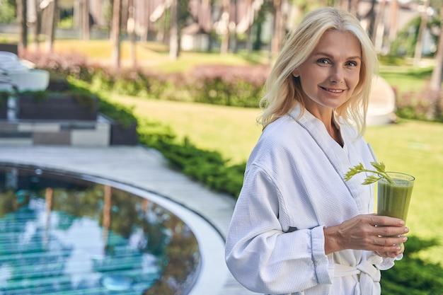 Linda mulher caucasiana relaxando com um copo de coquetel ao redor da piscina do hotel