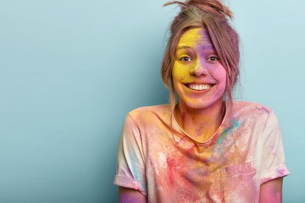 Linda mulher caucasiana se regozija ocasião festiva de holi na índia, tem tintura colorida no rosto e camiseta, parece feliz, tem um sorriso gentil, isolado sobre a parede azul. conceito de celebração de festival