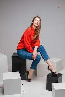 Linda mulher caucasiana sentada em cubos brancos e parece uma imagem isolada na parede branca
