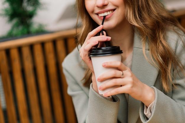 Linda mulher caucasiana tomando café em um café, sorrindo, falando ao telefone