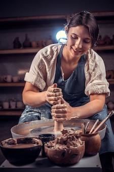 Linda mulher ceramista trabalhando na roda de oleiro com argila crua com as mãos