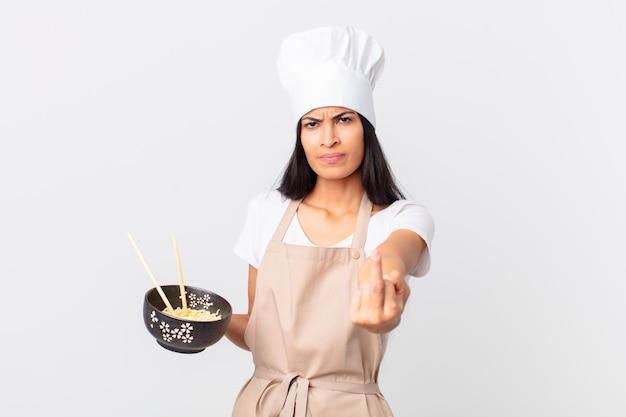 Linda mulher chef hispânica se sentindo irritada, irritada, rebelde e agressiva segurando uma tigela de macarrão