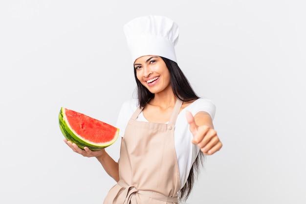 Linda mulher chef hispânica se sentindo orgulhosa, sorrindo positivamente com o polegar para cima e segurando uma melancia