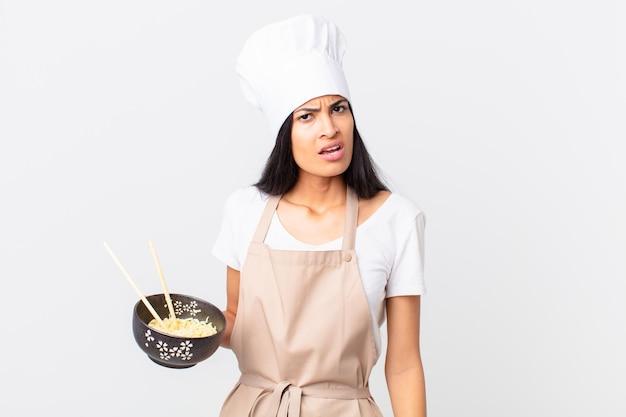 Linda mulher chef hispânica se sentindo perplexa e confusa e segurando uma tigela de macarrão