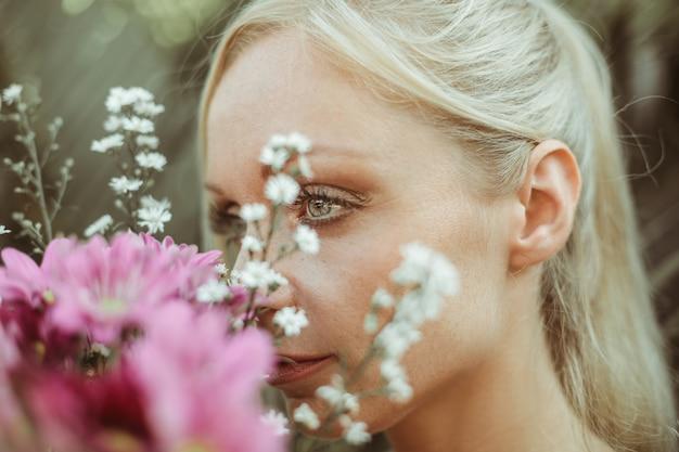 Linda mulher cheirando um buquê de flores