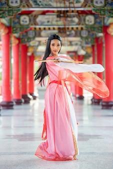 Linda mulher chinesa com um terno tradicional com golpe nas mãos dela.