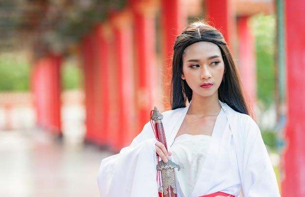 Linda mulher chinesa com um terno tradicional com uma espada afiada nas mãos dela.