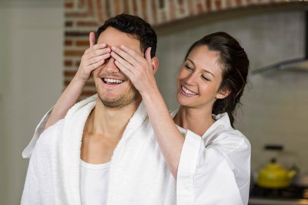 Linda mulher cobrindo os olhos do homem na cozinha