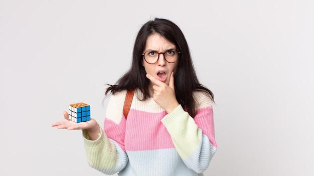Linda mulher com boca e olhos bem abertos e mão no queixo resolvendo um jogo de inteligência