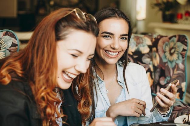 Linda mulher com cabelo comprido escuro olhando diretamente rindo enquanto segura um smartphone enquanto sua amiga está olhando para baixo rindo em um café.