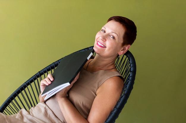 Linda mulher com cabelo curto, segurando uma revista