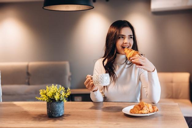 Linda mulher com cabelo preto brilhante, bebendo café durante o café da manhã. retrato interno de linda menina morena comendo croissant e desfrutando de chá de manhã.