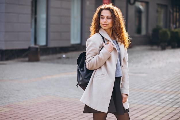 Linda mulher com cabelos cacheados, andando com um casaco de outono