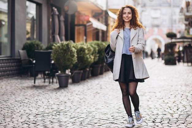 Linda mulher com cabelos cacheados, andando em uma rua de café