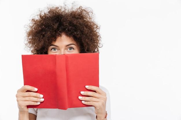Linda mulher com cabelos cacheados, espreitando de um livro