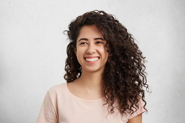 Linda mulher com cabelos crespos e crespos, mistura de nacionalidades, vestida de maneira casual, sorri amplamente, mostra dentes brancos perfeitos