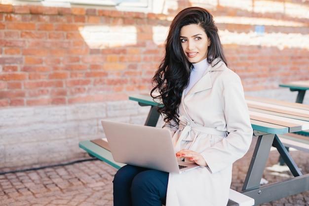 Linda mulher com cabelos ondulados escuros, vestindo capa de chuva branca, sentado no banco sobre a parede de tijolos, segurando laptop