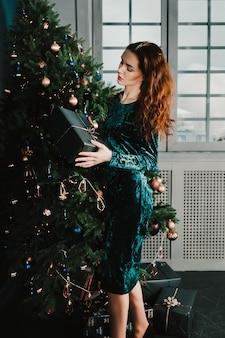 Linda mulher com caixa de presente perto de árvore de natal