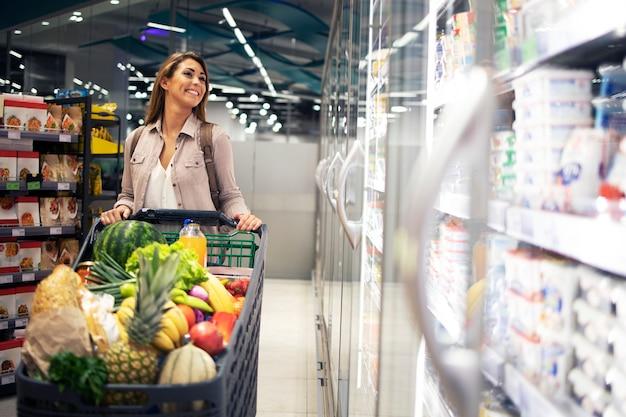 Linda mulher com carrinho de compras passando pelo freezer do supermercado e escolhendo o que comprar