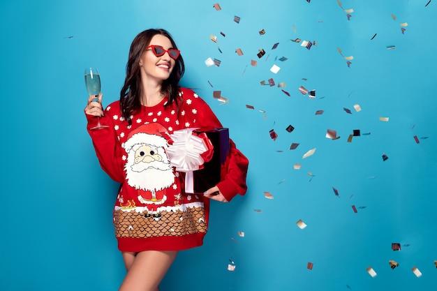 Linda mulher com champanhe em pé sob confetes caindo
