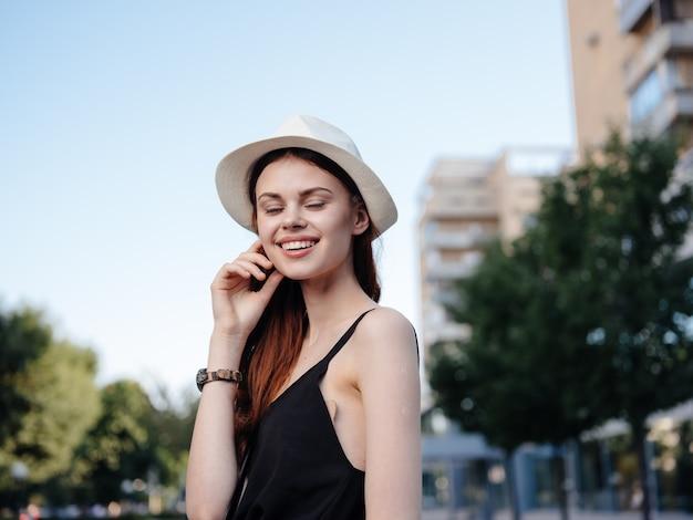 Linda mulher com chapéu ao ar livre na natureza, perto de edifícios.