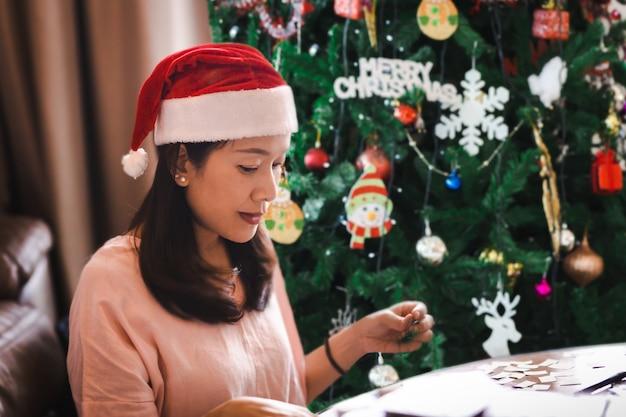 Linda mulher com chapéu de festa vermelha anta sentada perto da árvore de natal