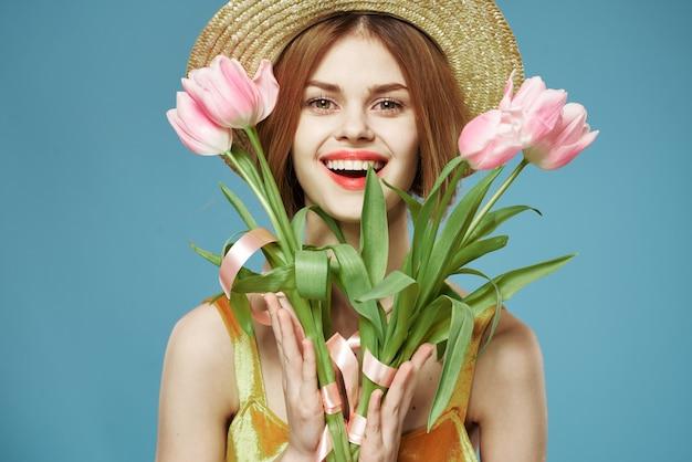 Linda mulher com chapéu de flores perto de fundo azul de sorriso de encanto de rosto. foto de alta qualidade