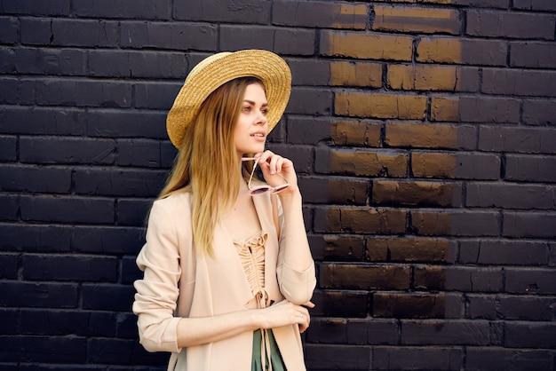 Linda mulher com chapéu de óculos escuros ao ar livre na parede de tijolos da cidade.