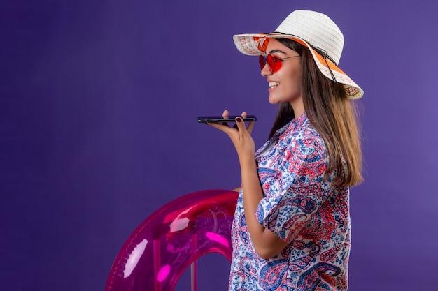 Linda mulher com chapéu de verão e óculos de sol vermelhos segurando um anel inflável, enviando mensagem de voz, usando o telefone celular, de pé de lado com o rosto feliz no espaço roxo