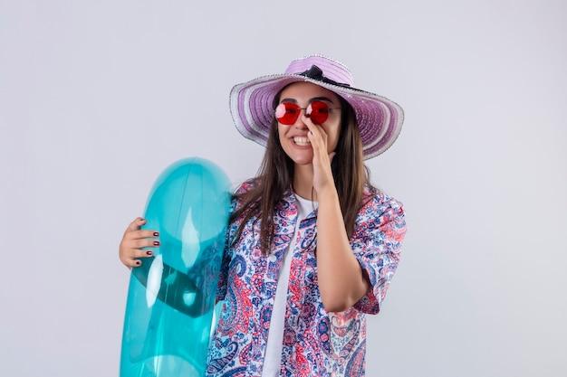 Linda mulher com chapéu de verão e óculos de sol vermelhos segurando um anel inflável gritando ou chamando alguém com a mão perto da boca positiva e feliz em pé