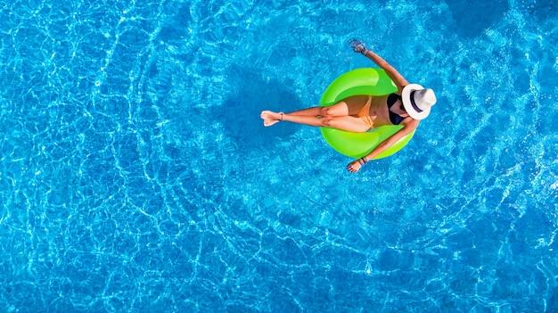 Linda mulher com chapéu na piscina no anel inflável na água nas férias