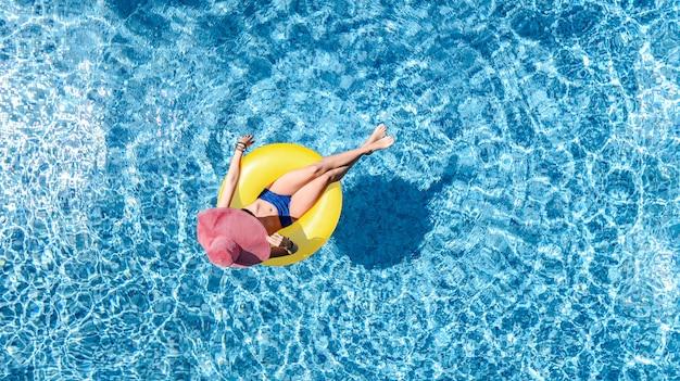 Linda mulher com chapéu na piscina, vista aérea de cima, jovem de biquíni relaxa e nada no anel inflável donut e se diverte na água, resort tropical de férias