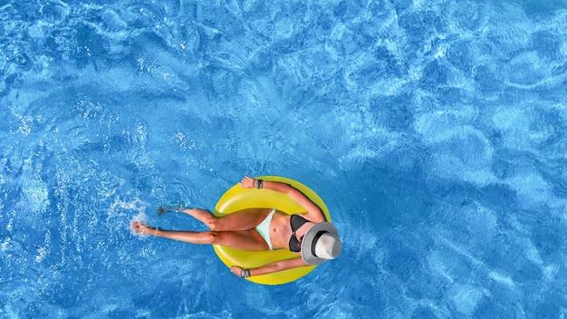 Linda mulher com chapéu na piscina vista aérea de cima, jovem relaxa e se diverte com o anel inflável na água nas férias