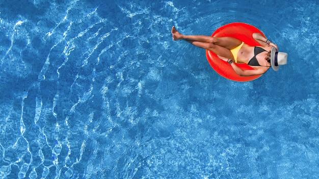 Linda mulher com chapéu na piscina vista aérea de cima, jovem relaxa e se diverte no anel inflável