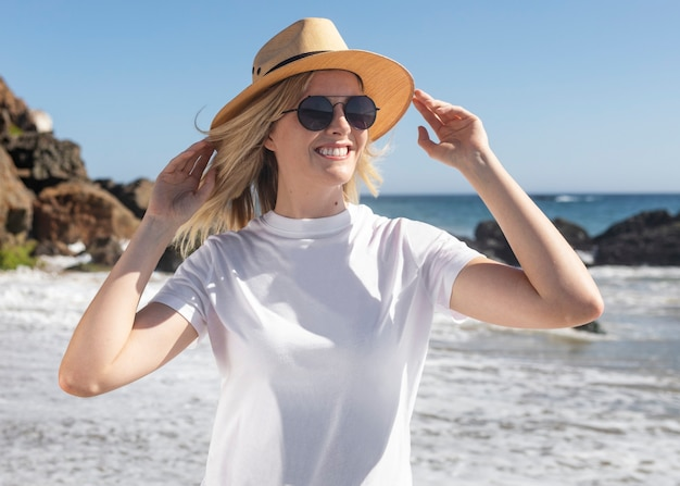 Linda mulher com chapéu-panamá relaxando na praia