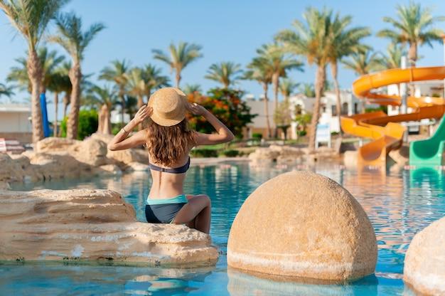 Linda mulher com chapéu senta-se na pedra perto da piscina spa. belo hotel exótico relaxe no egito. textura de água azul