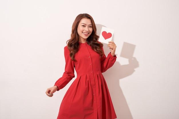 Linda mulher com coração vermelho isolado na parede cinza, celebração do dia dos namorados, sentimentos românticos, harmonia e conceito de amor
