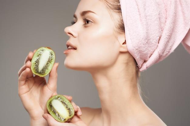 Linda mulher com corpo nu com fruta kiwi na mão cortada vista. foto de alta qualidade