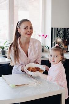 Linda mulher com criança adorável, segurando a tigela com biscoitos